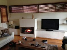 The recently completed installation of a Regency GF 900 L feature gas fireplace with logs and stainless trims. The fireplace was set into low entertainment cupboards with laminate doors and distressed. timber look tops.