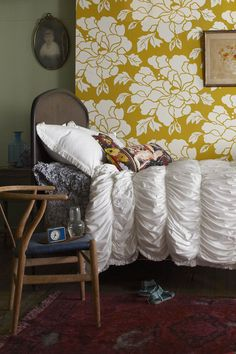 yellow peonies wallpaper, white bedding, rug, chair.