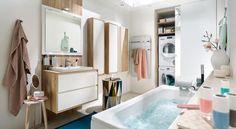 Signée Mobalpa, cette salle de bains associe le bois et le blanc dans un style contemporain et fait la part belle aux rangements, y compris une buanderie.