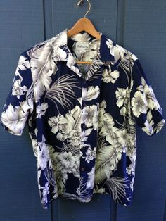 Did you know that Casual Friday began in the 1960s with Aloha Friday in Hawaii? This shirt could revive the tradition. Its classic all-over pattern of palm fronds and hibiscus flowers is printed in navy, taupe, white and light blue on soft cotton barkcloth, for a look thats cool and tropical without being over the top. Vintage detailing includes a notched collar, coconut shell buttons and a chest pocket so perfectly matched that it all but disappears. Its made in Hawaii by Bishop St, and is…
