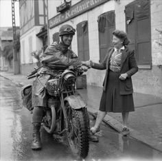 A motorcycle despatch rider greets Madame Scarlette, an Englishwoman who runs the Hotel des Fleurs in the village of Les Andelys, 31 August 1944.