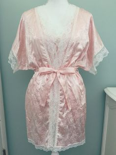 Beautiful pink vintage pajama set with shiny floral and ribbon pattern, white lace details, and interlaced ribbon design. Includes top, shorts, and robe.