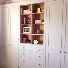 Farrow and Ball grey bedroom fitted wardrobes with shelves for displaying favourite things, like  lovely little Orla Kiely bits and pieces. Breaks up the space of wall to wall cupboards and makes a very personal space in a bedroom.  Furniture by Dunham Fitted Furniture