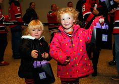 Two young fans hold up their bags with mystery pucks inside that were sold during New Jersey Devils' #HockeyFightsCancer Awareness Night.