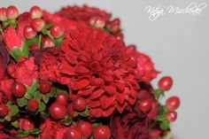 Bridesmaid bouquet - of red dahlia, red hypericum berries, red spray roses and red spray carnations.