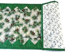 For your winter and holiday decor, this quilted table topper features a pine cone and pine bough print on an ivory tonal background. The pine print is framed by an evergreen tonal check print. The double fold binding is machine stitched on, then hand sewn to the backing, which is a n evergreen floral print on an ivory background. Reverse the runner after the holiday season.  Machine quilted. Table runner measures 14 x 32 1/2. Nicely sized for a dining room table, side board or buffet table…