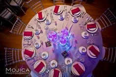 Indian wedding reception table with white linen red napkins and silver chiavari chairs