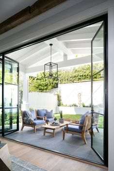 Folding glass patio doors open to a covered patio furnished with a teak slatted .Folding glass patio doors open to a covered patio furnished with a teak slatted coffee table placed on slate pavers beneath Folding Glass Patio Doors, Glass Doors, Outdoor Rooms, Outdoor Living, Outdoor Patios, Outdoor Kitchens, Outdoor Seating, Indoor Outdoor, Outdoor Decor