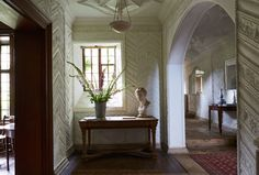 """Bridget Elworthy and her husband, Forbes, are devoted to their 16th-century stone manor, a large house with uneven floors and wings added over various ages. Against this structural backdrop, Elworthy mixes in artfully disheveled items such as fading chintz slipcovers or boldly painted furniture. """"It has the perfect combination of creative chaos and austere practicality,"""" writes Pentreath. The hall (shown) was an Arts and Crafts addition and features chalky-white molded plasterwork executed…"""