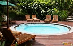 In ground Swimming Pool design with wood chair