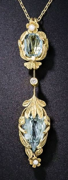 Arts & Crafts Aquamarine Pendant Necklace. A truly enchanting double-aquamarine pendant necklace dating from the turn-of-the-last-century. The gorgeous organically inspired jewel features a glistening pair of sky blue aquamarines (the bottom pear shape has a faceted top) enwrapped in high-karat golden leaves and dotted top and bottom with a tiny lustrous seed pearl and in the center with a tiny twinkling diamond. A rare and exemplary, original Arts & Crafts jewel.