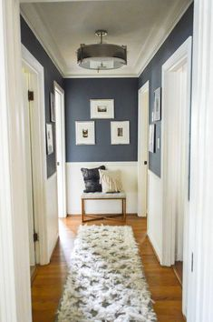 Love this idea for decorating in a hallway! Navy upper walls, white lower  and a small bench with pillows and picture frames at the end of the hallway.