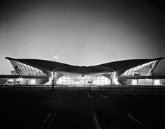 """In order to capture the concept of flight, Eero Saarinen used curves to create spaces that flowed into one another. The exterior's concrete roof imitates a bird in flight with two massive """"wings."""" The interior consists of a continuous ribbon of elements, all whisking themselves in from the exterior, so that ceilings continously run into walls and those walls become floors."""