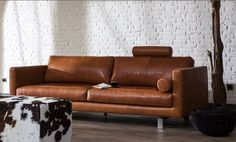 Cognac leather sofa contrasts with the white brick wall  www.mokana.nl