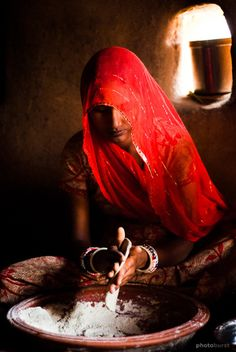Woman of Bishnoi making chapati in her traditional mud house.  Location: Rajasthan, India