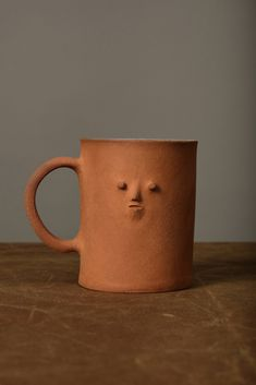 """Everyday mug with a mini face 3"""" x 4 1/2"""" x 3 3/4"""" Handbuilt with slabs Features warm sandy orange red ceramic body Glazed in white inside the cup Food safe Due to the handmade nature, there may be variations in size and color Hand washing is recommended Made in California Designer : Rami Kim Studio 