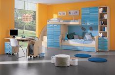 chambre enfant bleu, peinture murale jaune, pouf design, meubles en bois massif et sol en gris taupe