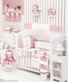 enxoval de bebê delicado com arabesco, flores e bonecas na cor rosa e branco cheio de babados. O berço conta com um mosquiteiro lindo.