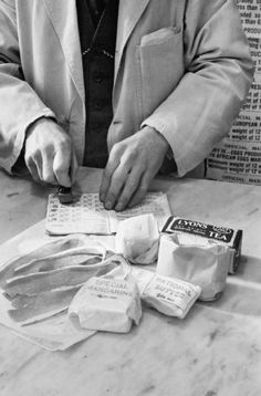 British shopkeeper with WWII ration book. Shown is a weekly ration of tea, sugar, butter, margarine, cooking fats, and bacon.