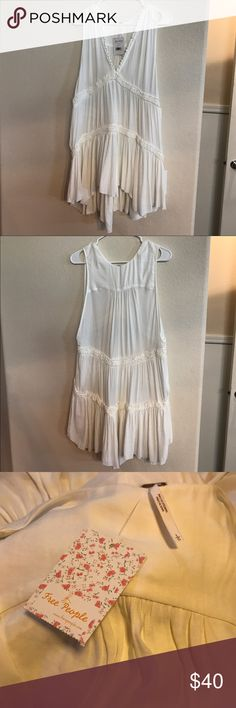 """NWT Free People Tunic Top This long sleeveless shirt has never been worn and comes NWT. Was a gift but is too big on me. Longer in the back at 35"""" and shorter in the front at 30"""" (both measurements taken from the shoulder). Color is Ivory. Free People Tops Tunics"""