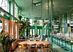 Dutch design office Studio Modijefsky has filled an Amsterdam bar with tropical plants and green surfaces to create a rainforest-like feel