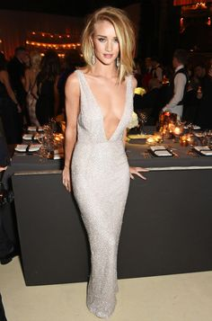 Look da modelo Rosie Huntington-Whitely usando vestido prateado com super decote.