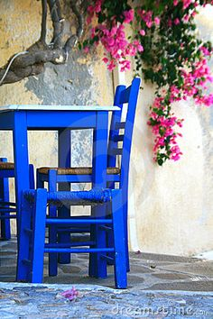 Chairs and table and bougainvillea in the background from traditional Greek taverna from Ano Syros on the island of Syros, Greece