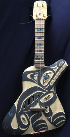 Made in Canada by a First Nation Luthier (and I think it represents a fox?) --- https://www.pinterest.com/lardyfatboy/