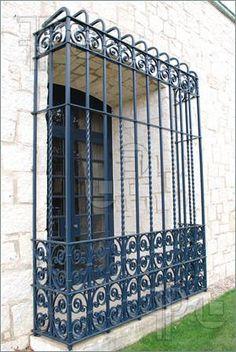 Imagen de una característica bienes españoles de elegante arquitectura de hierro forjado a través de una ventana.
