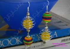 Each of this pair of earrings has a round lemon Yellow Glass bead of 16 mm, enclosed in Non Tarnish Silver Plated Copper Wire, and a Rainbow Colored Thread Ball also of 16 mm. Two Faceted Silver Crystal Beads are placed above and below the Wired Glass Beads.