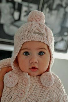 adorable sweater, buttons great....pompoms on ends of knit hat.... not to mention the big eyed little gal... so attentive to the camera... cutey pie