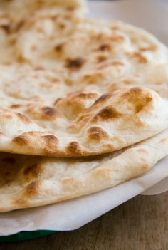 Garlic Naan  Ingredients:  1 teaspoon active dry yeast  1/2 cup warm water  1 tablespoon granulated sugar  1 teaspoon salt  1/4 cup soy milk  2 cups bread flour plus more for kneading  3 tablespoons minced garlic  Grapeseed oil