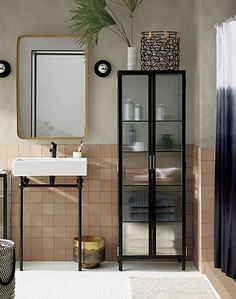 """modern apothecary. As noted by the designer Ceci Thompson, this piece """"is an industrial take on vintage pharmacy cabinets."""" Ideal in any sized bathroom, fluted glass panes obscure contents but keep things visually light. Two doors open to reveal five glass shelves for a considerable amount of storage. We also love it as an impromptu linen """"closet"""" in the hall. Learn about Ceci Thompson on our blog."""