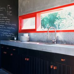 modern black kitchen with concrete counters and bright red-orange window frame as a bright and bold kitchen focal point. big chalkboard wall