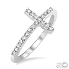 This Diamond Cross Ring Will Mesmerize. Styled In Lustrous 10 Karat White Gold This Brightly Shining Ring Features A Simple Cross Embellished With 20 Prong Set Round Cut Diamonds. Total Diamond Weight Is 1/5 Ctw. Price: $429.00