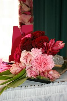 Bouquet mix of roses and tropicals in a pink ombre color palette.