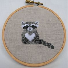 This is an original counted cross stitch pattern of a raccoon with a cute heart on its chest. The pattern has been shown stitched on 32 count