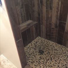 Barn wood tile shower with pebbles on the floor.