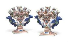 A PAIR OF DUTCH DELFT POLYCHROME TULIPIERES  EARLY 18TH CENTURY, IRON-RED VE, I AND O MARKS FOR LAMBERTUS VAN EENHOORN AT DE METALEN POT  Each of flattened heart shape, surmounted by eight spouts and flanked by winged bird handles, painted to one side with a flower-filled urn, the reverse with flowering trees in landscape, the rectangular base painted with birds and lotus  8 in. (20.3 cm.) high (2)