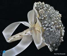 This pearl and crystal brooch bouquet features a variety of bright pearl and crystal brooches. Its finished with a large ivory satin bow and rhinestone