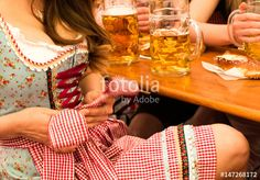Beautiful young woman fixing her Dirndl at Munich Oktoberfest