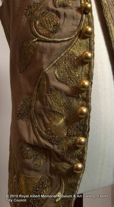 Detail of metal gilt thread embroidery and metal buttons of child's waistcoat, 1727-1760, England, silk (corded), Metal gilt (threads and spangles). Royal Albert Memorial Museum & Art Gallery