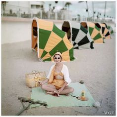 Model on beach in front of the Diplomat Hotel, Florida, in calico print swimsuit and terrycloth cardigan, 1959