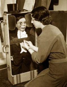 Edgar Bergen's secretary placing Charlie McCarthy in his special suitcase