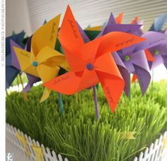 Miniature pinwheel escort cards in bright purple, orange and blue on a bed of wheatgrass.