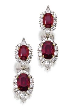 Pair of platinum, ruby and diamond earrings. Set with cushion-shaped rubies weighing approximately 11.00 carats, framed by round and pear-shaped diamonds weighing approximately 6.30 carats, pendants detachable.