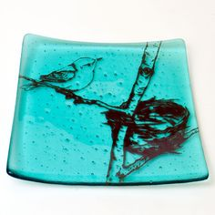 This platter features our warbler and nest drawing screen printed in brown enamel onto transparent aqua glass, then fused in a kiln to about 1400 degrees. After that, it is cold-worked on glass saws a