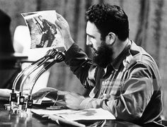 The dictator Fidel CASTRO announcing over the radio in Cuba the death of CHE GUEVARA, his companion in arms, in the Bolivian jungle. He is showing a photo of the guerilleros.