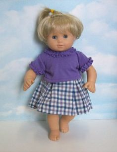 """Purple Ruffled Shirt and Skirt Set. Fits 15"""" Dolls like Bitty Baby® and Bitty Twin® by Small Small World. $19.99. Two piece set.. Purple top with ruffle trim.. Checkered skirt.. ***Doll NOT Included***. Matching outfits for 15"""" boy doll and 18"""" girl doll also available."""