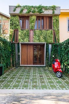 Modern facade of wood slats, concrete, and vegetation at Casa Goia help screen the facade for privacy and shading in San Paolo. By Renata Pati